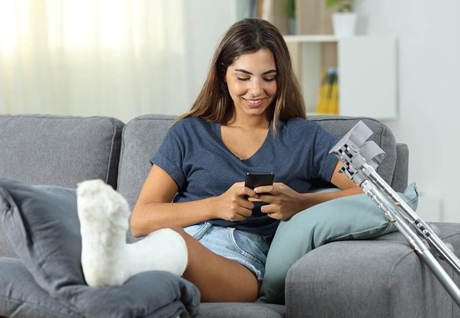 Gipszelt lábú lány ül az ülőgarniturán és SMS-t küld